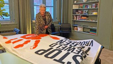 Wethouder Konijn-Vermaas met de 'Orange the World' -vlag