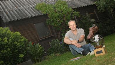 Henk van den Bosch voor de houten garage bij zijn ouderlijk huis.