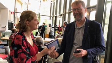 Redacteur Alfred Valstar overhandigt het boek El Mundo aan kunstenares Henrieke Krijgsheld.