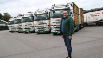 Gertjan Tomassen bij de net afgeleverde nieuwe vrachtwagens.