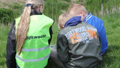 Kinderen in actie bij een dijk.