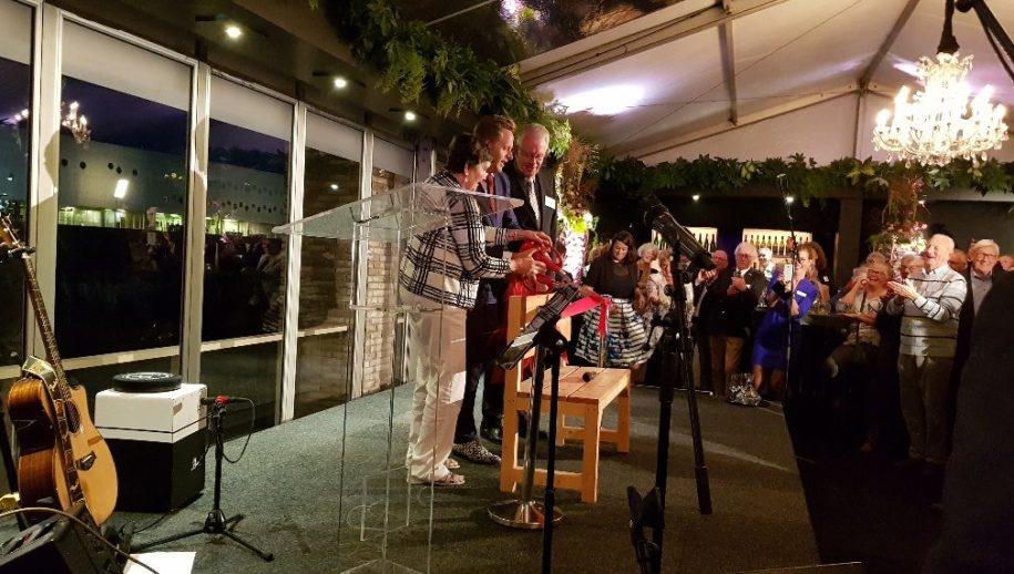 De minister knipt het lintje door samen met twee bewoners.