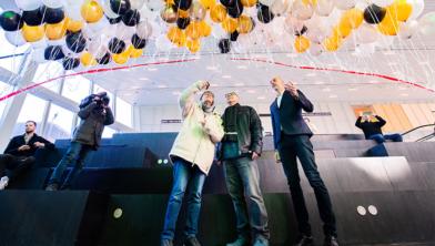Ellen (miljoenste bezoeker) en Willem Dijkstra knippen het lint met ballonnen door.