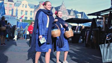 Bloemenmeisjes flyeren bij de Grote Markt in Haarlem voor '3x7.'
