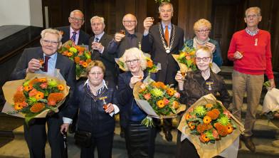 De negen gedecoreerden en de burgemeester toosten.