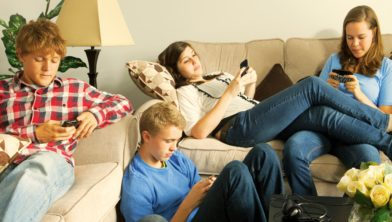 Teenagers texting on mobile phones in a home setting