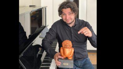 'Pianoman' Ivo Rosbeek met zijn Lexor Award eert het voormalig theater aan de Willemstraat in Heerlen.