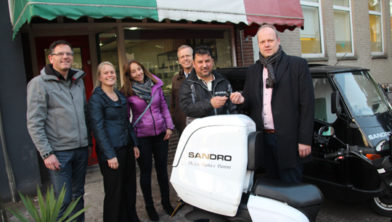 Wethouder Tigelaar neemt de sleutel in ontvangst van de eigenaar van Pizza Sandro op de Utrechtseweg, die de scooter als laatste leende.