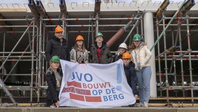 JvO-leerlingen hangen bouwvlag op het middenschip van hun school in aanbouw