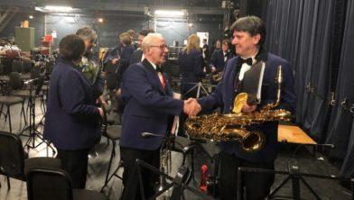 Cees Groen 70 jaar lid van muziekvereniging Sint Caecilia wordt door zijn medemuzikanten gefeliciteerd