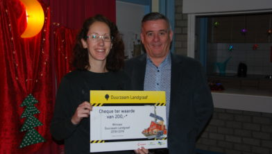 Juffrouw Lionne Logister van groep 6a van OBS de Speurneus ontvangt de cheque van wethouder Freed Janssen.