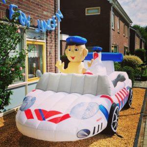 opblaas-politieauto met baby en ooievaar in voortuin.