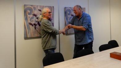 Theo Gaasbeek (l) reikt een zilveren theelepel met vogelmotief uit aan 100e abonnee dhr. P.J.