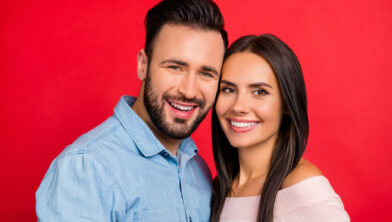 Close up portrait of smiling, beautiful, couple, looking at camera, head to head bonding, standing over red background, 14 february