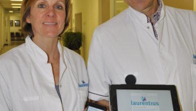 Oncologisch chirurg Sofie Fransen en Internist oncoloog Marien den Boer tonen trots de Laurentius Behandelwijzer App.