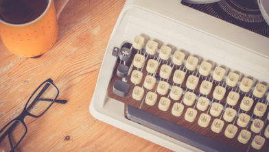 Vintage typewriter, glasses and cup of coffee on a wood desk