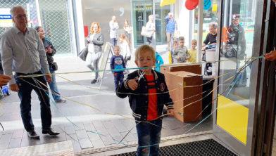 Ondernemer Wil Meijers kijkt toe hoe een jonge klant de nieuwe Top1Toys opent.