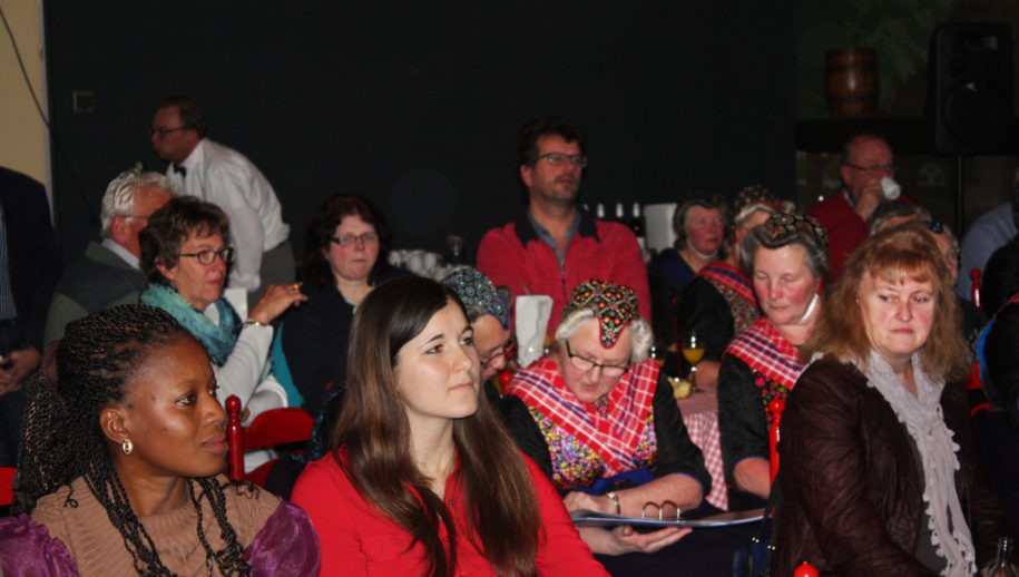 De aanwezigen in de zaal luisteren naar de informatie. Mevrouw Patience Jatta luistert ook.