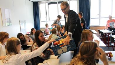 Wethouder Krale deelt appels uit in een klas van de Pieter Zandt