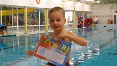 Zwemleerling Lukas de Groot toont zijn behaalde diploma