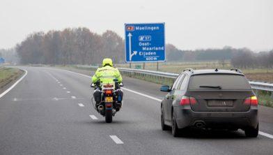 Motoragent rijdt naast auto op snelweg