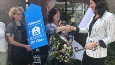 Gedeputeerde Monique van Haaf overhandigt sleutel aan winnares Kitty Vos.