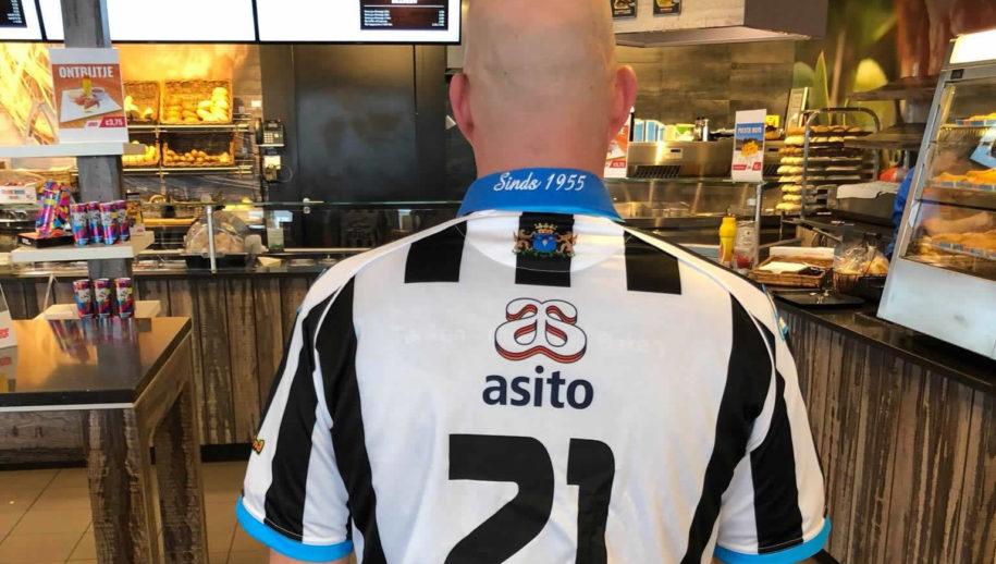 Björn Spoor toont de achterkant van het Heracles-shirt dat hij draagt
