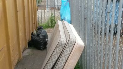 Gedumpte matrassen bij een papiercontainer