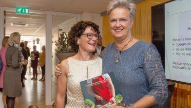 Janny van de Laar (l.) overhandigt haar eerste boek aan patiënte Marie-Joze van Riel