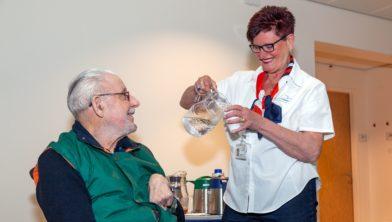 Gastvrouw Ria van Rijen biedt een wachtende patiënt iets te drinken aan