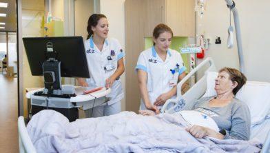 Verpleegkundigen Eline van Kroonenburg (l.) en Jisse Warmerdam beoordelen samen een patiënt.