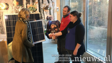 Wethouder Kammeijer reikt het zonnepaneel uit.