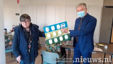 Burgemeester Frank Petter krijgt een canvas met een verhaal cadeau, gemaakt door de bewoners.