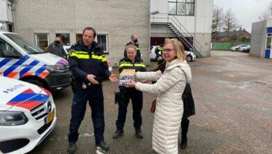 Burgemeester Van Beek overhandigt de taarten aan de politie.
