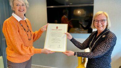 Hannie Zwinkels (l) krijgt de oorkonde van burgemeester Marijke van Beek.