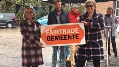 Burgemeester Van Beek krijgt het bord van Fairtrade Gemeente. In het midden wethouder Burgers