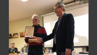 Voorzitter Piet Wieringa feliciteert Klaas Loonstra