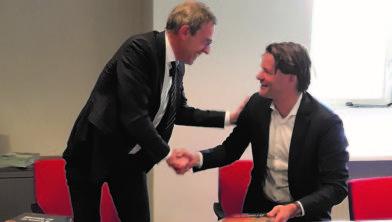 Burgemeester Bolding geeft de SG Schurink een exemplaar van Op verkenning in Het Hogeland.