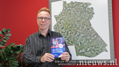 Wethouder Lars van der Beek presenteerd het boekje '|Sport in Woensdrecht'