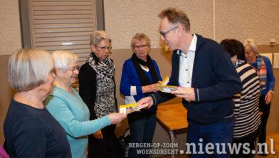 Wethouder Lars van der Beek deelt de seniorengids uit
