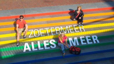 Enkele reizigers op station Centrum West bij de beroemde regenboogtrap van Zoetermeer