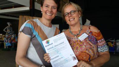 Sandra van der Geer en Christine Advokaat presenteren de nieuwsbrief aan werkers in de wijken Centrum, Dorp, Palenstein en Driemanspolder.