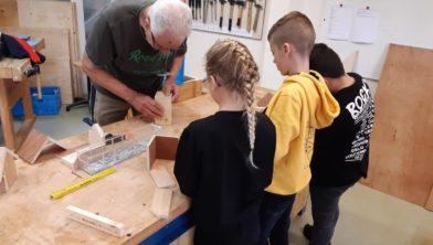 Kinderen gaan onder leiding van een leermeester houtbewerking aan de slag met het maken van hun eigen vogelvoerhuisje.