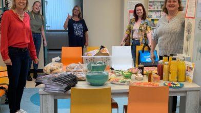Kookvrijwilligers Sandra en Karlijn, wethouder Ingeborg ter Laak en Fransesca van Franseca Kookt! overhandigen de paasbrunch aan de manager van de huisartsenpost.