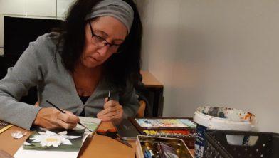 Een deelnemer is geconcentreerd aan het werken aan haar kunstwerk.