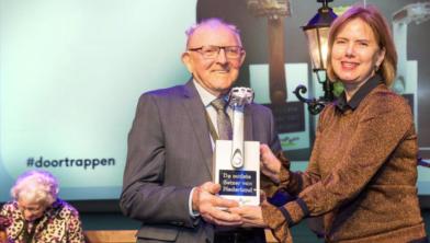 Egbert Brasjen krijgt de zilveren trapper uit handen van minister Cora van Nieuwenhuizen