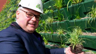 Wethouder Ed Anker plaatst de laatste plantjes tegen de gevel