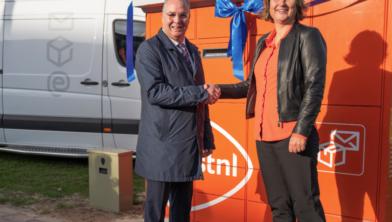 Wethouder William Dogger en PostNL-manager Jiska Stuurman nemen de pakket- en briefautomaat feestelijk in gebruik.