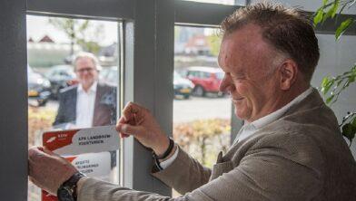 Directeur Hans Quint van Abemec plakt de erkenningssticker op het raam