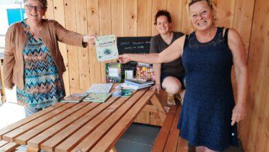 Bibliotheekmedewerker Aafke overhandigt de boeken aan vrijwilliger Annette.